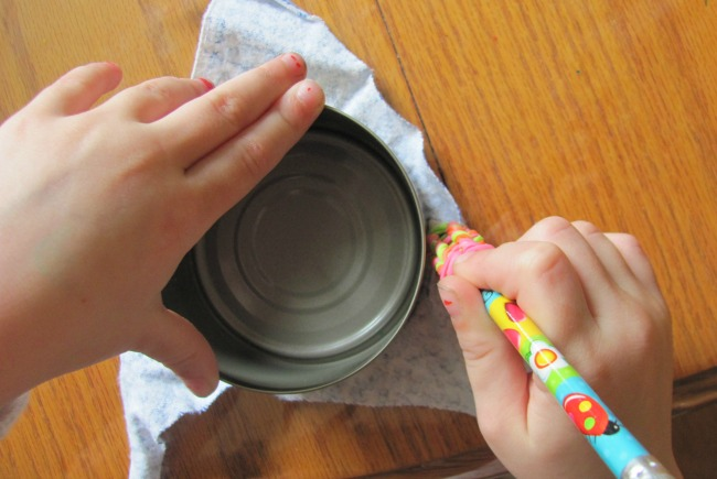 Child tracing a tin can on fabric